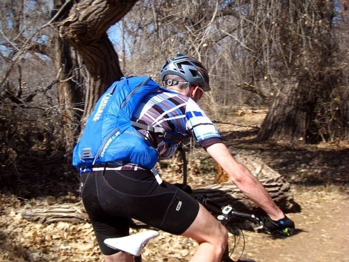 Cyclist wearing CamelBak hydration pack while riding through woods