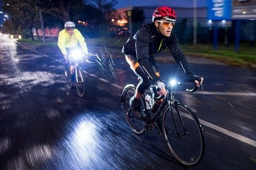 Two men riding a bike with lights.