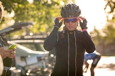 Woman putting on eye protection before going cycling.