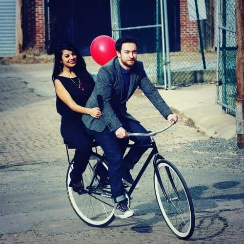 Men and woman riding on a bike.
