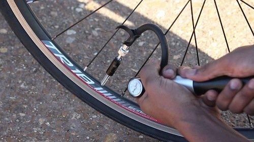 Pumping a bike tire.