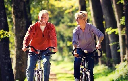 Senior men and woman riding a bike.