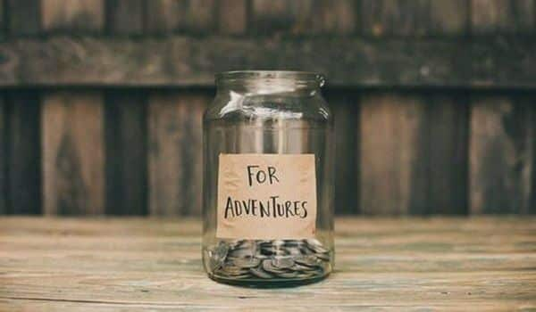 Jar containing money for the next adventure on the wooden table