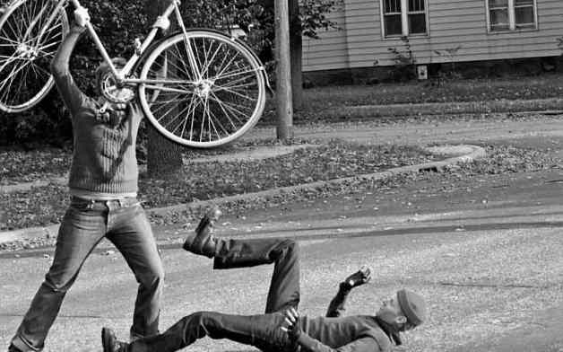 Cyclist attacking man with a bike