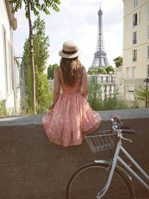 Girl sitting and watching the Eiffel Tower with bike parked next to her