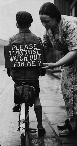 Boy on a bike with his mother wearing a sign about safety