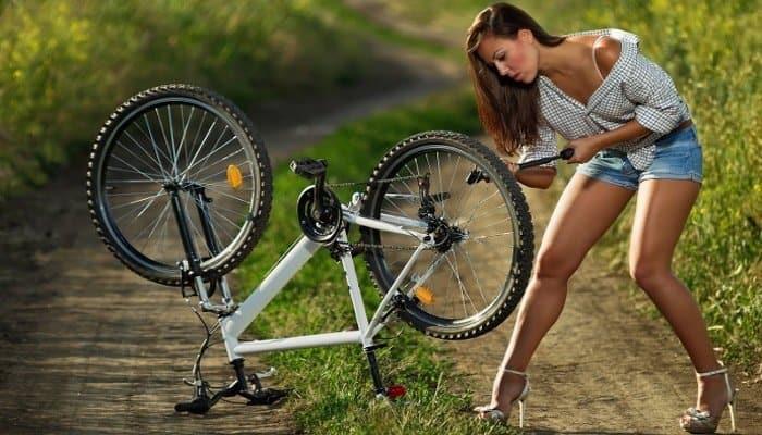 Woman fixing flat bike tire