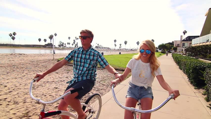 Young couple riding bike on a beach