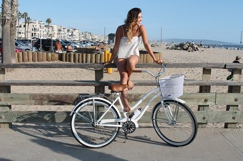 Woman sitting on a fence next to white beach cruiser bike