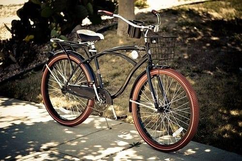 Black Huffy cruiser bike on a sidewalk