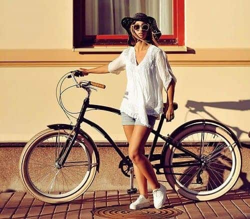 Woman holding black multi speed cruiser bike