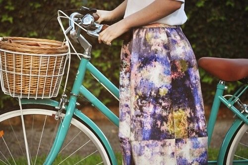 Woman holding teal cruiser bike with a basket