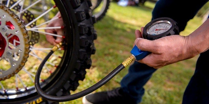 Checking bike tire pressure with a gauge.