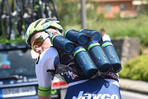 Cyclist with bottles of water on his back.