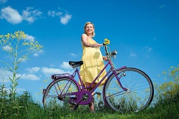 Pregnant woman next to a bike.